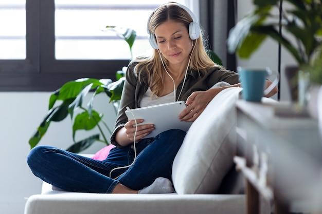 집에서 소파에 앉아 있는 동안 헤드폰과 디지털 태블릿으로 음악을 듣는 예쁜 젊은 여성의 사진.