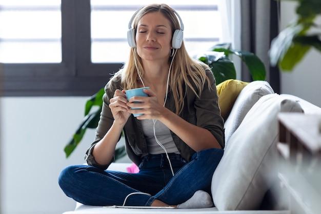 집에서 소파에서 커피 한 잔을 마시는 동안 헤드폰으로 음악을 듣는 예쁜 젊은 여성의 총.
