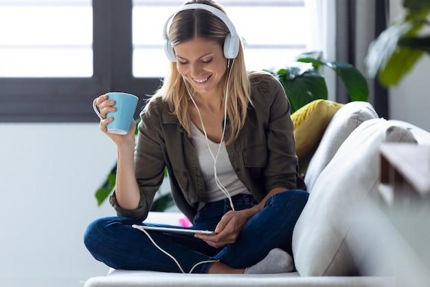 집에서 소파에서 커피 한 잔을 마시는 동안 디지털 태블릿으로 음악을 듣고 있는 예쁜 젊은 여성의 사진.