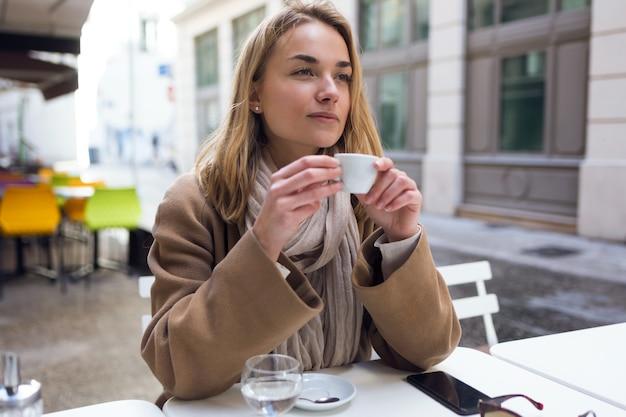 Выстрел из красивой молодой женщины, глядя в сторону, попивая чашку кофе на террасе кафе.