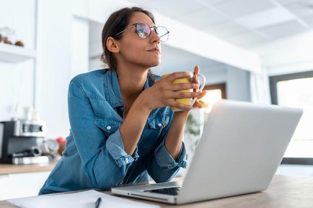 自宅のキッチンでノートパソコンを操作しながら、一瞬リラックスしてコーヒーを飲むかなり若い女性のショット。