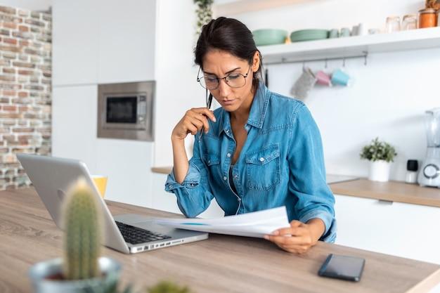 書類を確認し、自宅のキッチンでラップトップで作業しているかなり若い女性のショット。