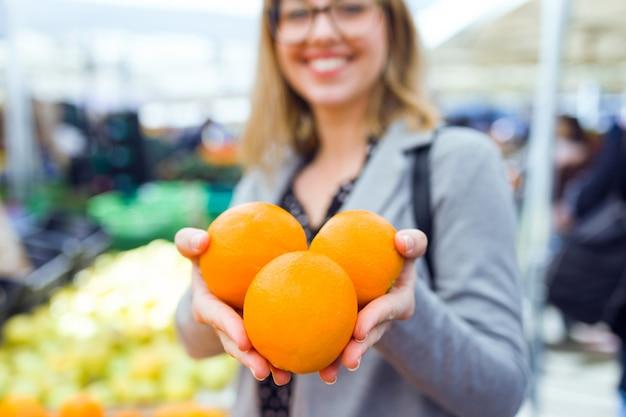 Выстрел из довольно молодой женщины, показывая апельсины на камеру на уличном рынке.