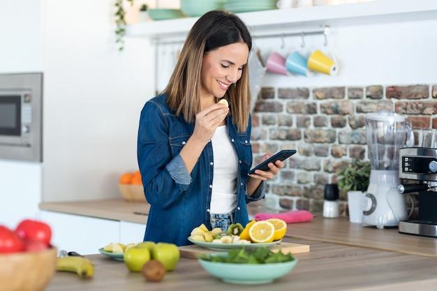 Снимок красивой молодой женщины, использующей свой мобильный телефон во время еды кусочка банана на кухне дома.