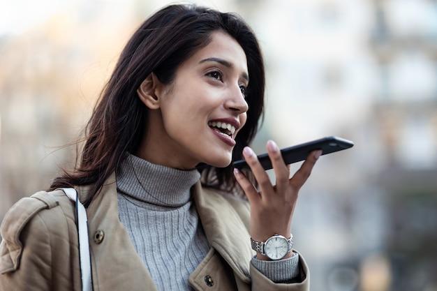 Снимок красивой молодой женщины, использующей систему распознавания голоса на своем смартфоне, стоя на улице.