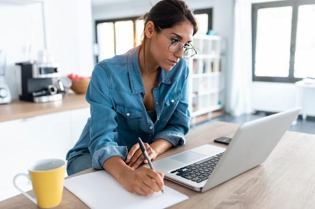 かなり若い女性がメモを書き、自宅のキッチンでラップトップで作業しているショット。