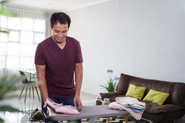 家事で忙しい責任ある夫や独身男性のショット、朝、仕事の前にアイロン台でシャツにアイロンをかける、