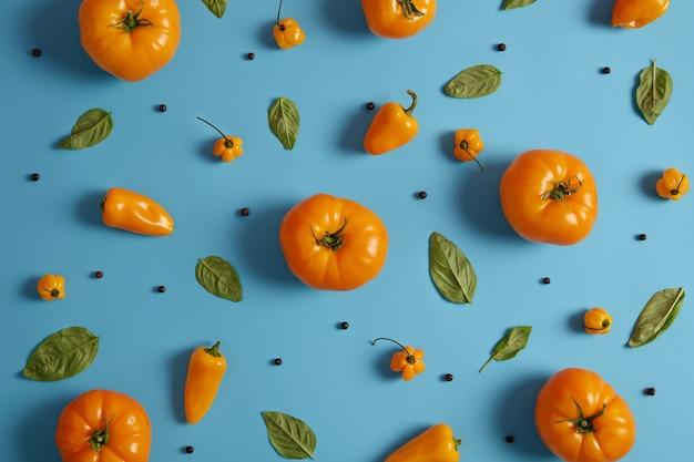 青の背景に熟した黄色いトマト、パプリカ、コショウの実、バジリックの緑の葉のショット。ベジタリアン料理を調理するための新鮮な野菜やスパイスのコレクション。自然食品の概念
