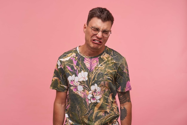 Выстрел грустного плачущего молодого человека в очках, одетого в цветную футболку, выглядящего несчастным и расстроенным, стоящего на розовом фоне, концепция отрицательных эмоций