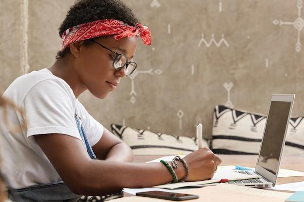 真面目なアフリカ系アメリカ人の学生のショットは、研究を行うためのメモを作成します