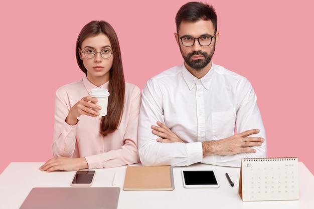 Снимок серьезных перфекционистов женского и женского пола, хорошо организованных, в очках, на рабочем месте все на своем месте, пьющих кофе, работающих вместе над новым проектом, изолированные на розовом