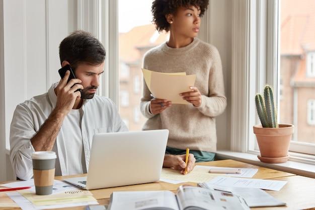 電話での会話中の深刻な男性のメモ情報のショット
