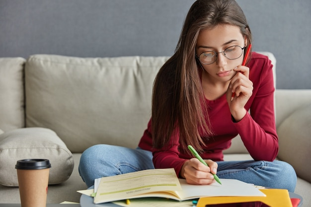 Снимок серьезного опытного студента с ручкой в руке, который пишет биографические данные