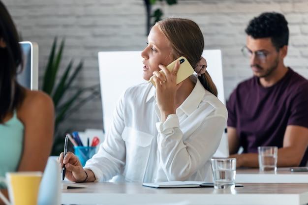 オフィスで彼女のコンピューターを操作しながら携帯電話で話している賢い実業家のショット。