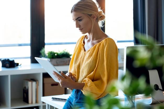 彼女のスタートアップ中小企業でデジタルタブレットを使用して作業しているスマートなフリーランスのビジネスウーマンの売り手のショット。