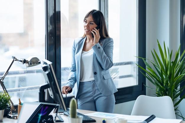 現代のワークスペースの窓から見ながら立っている間、彼女の携帯電話で話している賢い若い実業家のショット。