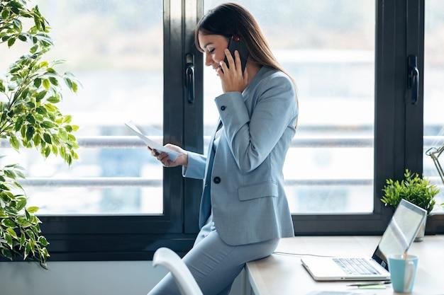 現代のワークスペースでいくつかのドキュメントを頬にしながら携帯電話で話しているスマートな若い実業家のショット。