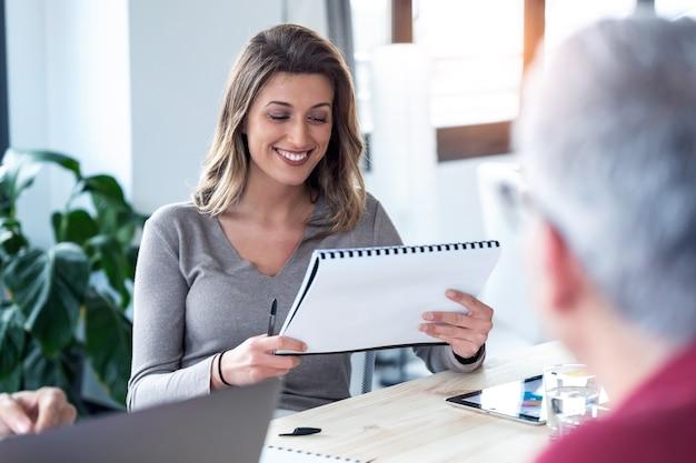 코워킹 스페이스에서 회의를 위해 메모를 검토하는 웃고 있는 비즈니스 여성의 샷.