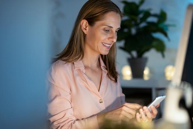 사무실에서 컴퓨터로 작업하는 동안 스마트 폰을 사용하여 웃고 있는 성숙한 비즈니스 여성의 샷.