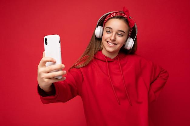 Выстрел улыбающейся красивой девушки брюнетки в красной толстовке с капюшоном, изолированной на красном фоне, держащей и использующей