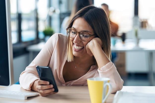 現代のスタートアップオフィスに座って携帯電話でメッセージを送信する笑顔の若いビジネス女性のショット。