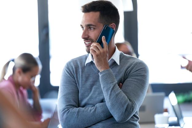 コワーキングスペースで携帯電話で話している笑顔の青年実業家のショット。
