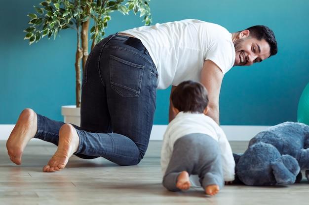 웃고 있는 젊은 아버지의 샷은 집에서 함께 바닥에 기어가는 동안 어린 아기와 즐거운 시간을 보냅니다.