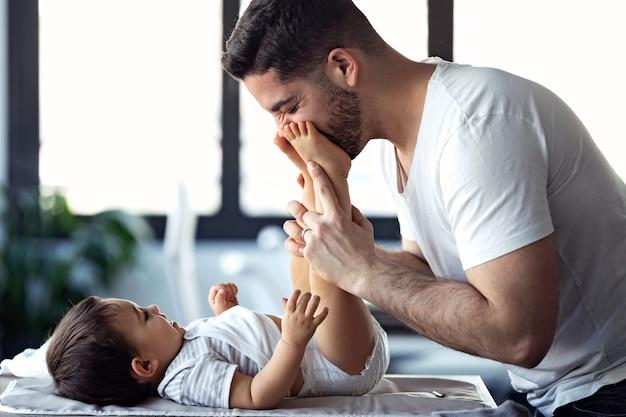 웃고 있는 젊은 아버지의 사진은 집에서 기저귀를 갈아주는 동안 어린 아기와 즐겁게 놀고 있습니다.