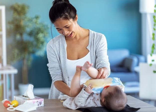 웃고 있는 젊은 어머니의 샷은 집에서 기저귀를 갈아주는 동안 어린 아기와 즐겁게 놀고 있습니다.