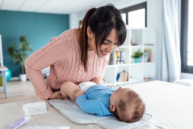 笑顔の若い母親のショットは、家でおむつを変えながら小さな赤ちゃんと一緒に楽しんでいます。