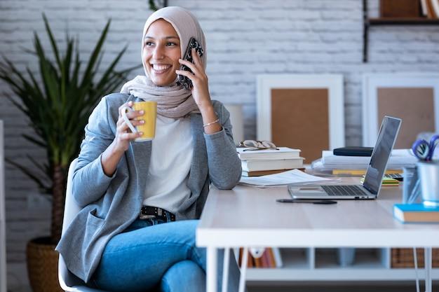 사무실에 앉아 휴대 전화로 얘기 하는 hijab을 입고 웃는 젊은 이슬람 비즈니스 여자의 쐈 어.