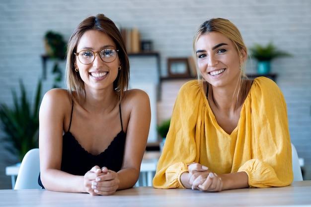 彼女のスタートアップ中小企業でビデオ会議をしながらウェブカメラを見て話している笑顔の若い女性のショット。