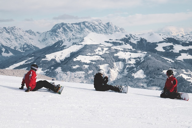 スノーボーダーが雪の上に座って、オーストリアのチロルの白い山を見てのショット