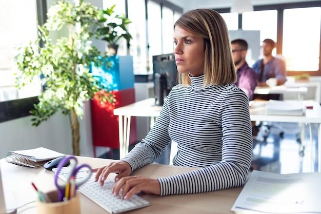 現代のスタートアップオフィスでコンピューターを操作しているソフトウェア開発者のショット。