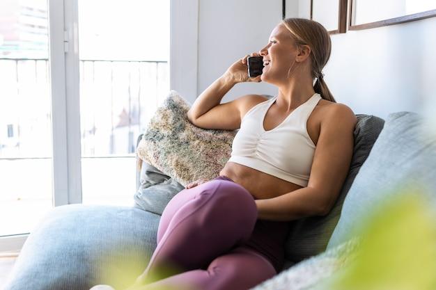 自宅の居間でソファに座って携帯電話で話しているスポーティな幸せな女性のショット。