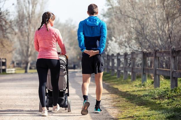 散歩しながらストレッチしながら屋外で一緒に時間を楽しんでいる幼い息子と一緒にスポーティな若いカップルのショット。