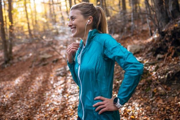 가을 아침에 공원에서 달리기를 한 후 휴식을 취하면서 음악을 들으며 스포티한 젊은 여성의 사진.