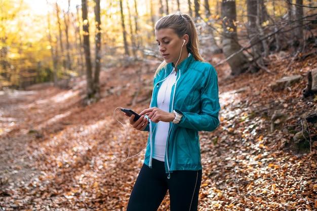 가을 아침에 공원에서 달리기를 한 후 휴식을 취하는 동안 휴대전화를 사용하는 스포티한 젊은 여성의 사진.