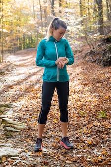 Снимок спортивной молодой женщины, использующей свои умные часы перед бегом в парке осенним утром.