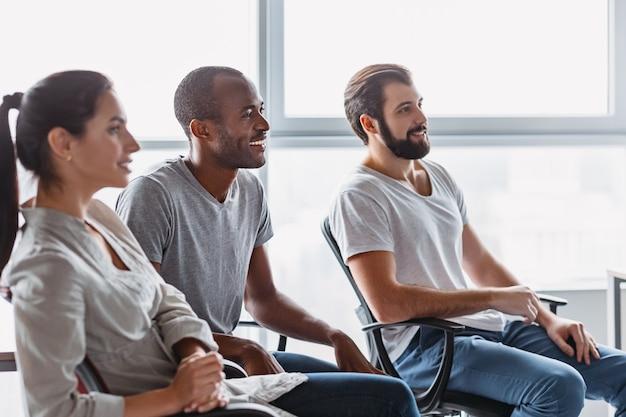 スタートアップビジネスチームがブレーンストーミングを行い、ビジネストピックについて話し合うショット。新しいビジネスプロジェクトのためにオフィスで一緒に働いている3人。彼らは上司に耳を傾けます