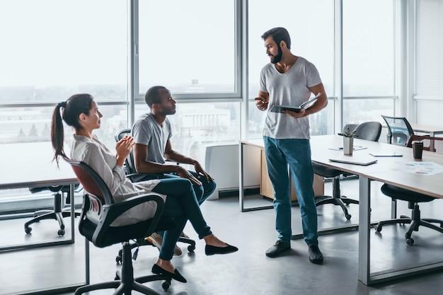 スタートアップビジネスチームがブレーンストーミングを行い、ビジネストピックについて話し合うショット。新しいビジネスプロジェクトのためにオフィスで一緒に働いている3人。