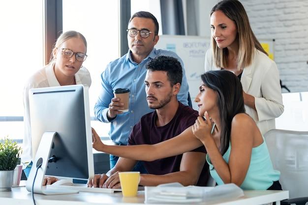 コワーキングスペースでの作業のプレゼンテーションのためにコンピューターの周りに立っている成功したビジネスチームのショット。