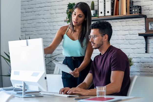 사무실에서 컴퓨터 디지털 태블릿과 함께 일하는 성공적인 비즈니스 팀의 샷.
