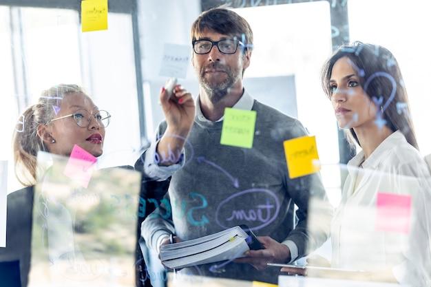 Выстрел успешной бизнес-команды, пишущей заметки на стеклянной доске офиса во время совместного обсуждения в коворкинге.