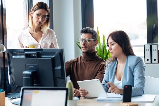 Выстрел успешной молодой бизнес-команды, стоящей вокруг компьютера, делая видеозвонок в коворкинге.