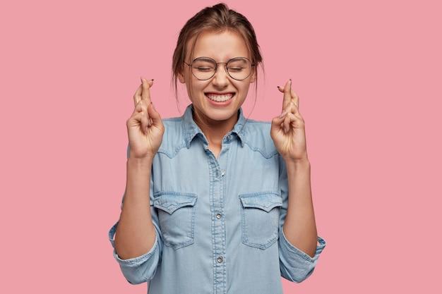 Суеверная женщина с веселым выражением лица скрещивает пальцы на удачу