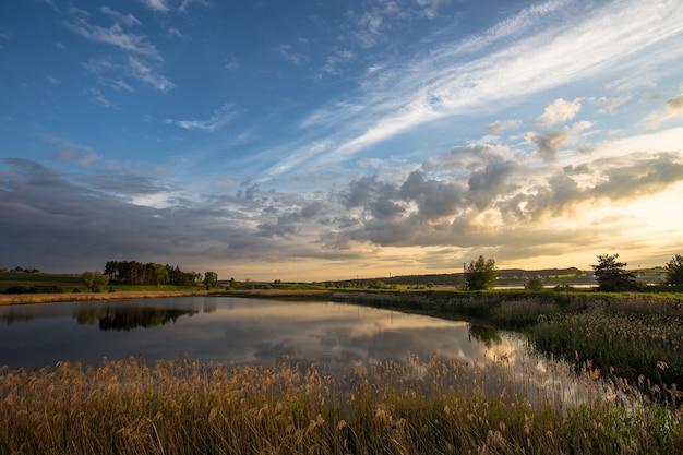 ポーランド、トチェフの日没時の牧草地にある小さな池のショット