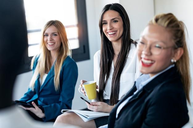 オフィスで微笑んでいる間彼女の同僚を探している3人のエレガントな若いビジネスウーマンのショット。