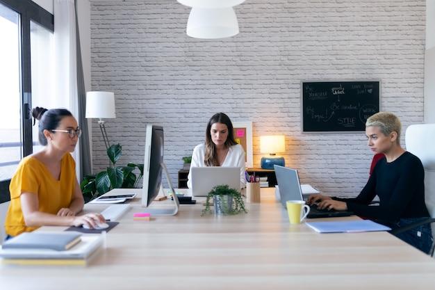 コワーキングスペースで新しいアイデアに取り組んでいる3人の現代の起業家の女性のショット。