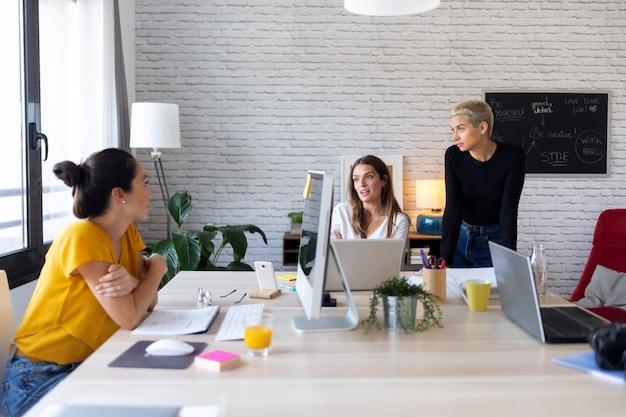 Снимок трех современных женщин-предпринимателей, которые рассказывают о новых идеях для следующей работы в совместном рабочем пространстве.